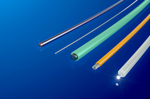 Coating wires and fibers by means of thermoplastic extrusion
